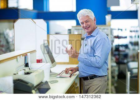 Portrait of pharmacist making prescription record through computer in pharmacy