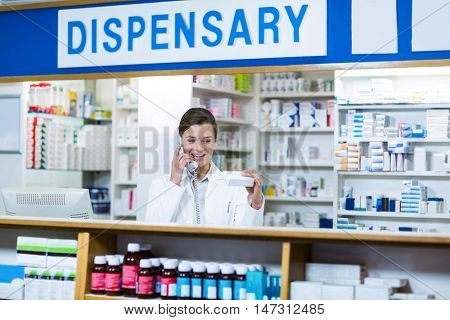 Pharmacist looking at medicine box while talking on phone in pharmacy