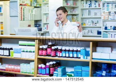 Pharmacist holding medicine box while talking on phone in pharmacy