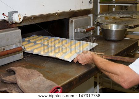 Bakery Production. Man, Baker, Placing The Cakes In The Oven