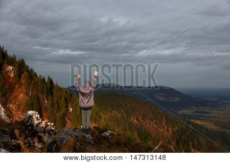 hiker with hands up stands on a hill