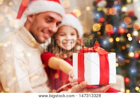 family, christmas, holidays, happiness and people concept - close up of smiling daughter giving father gift box
