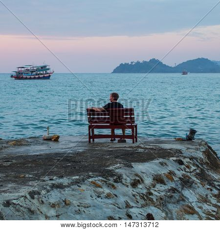 A young man sits alone on a stone cliff of the sea coast in the twilight.