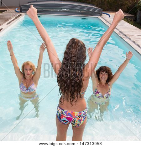 Happy Fitness Class Doing Aqua Aerobics In Swimming Pool