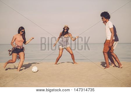 Active games with friends. Group of cheerful young people playing with soccer ball on the beach with sea in the background