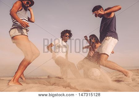 Beach ball fun. Group of cheerful young people playing with soccer ball on the beach