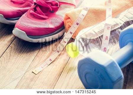 Sneakers, Towel, Water, Tape Measure, And Dumbbell On Wooden Floor