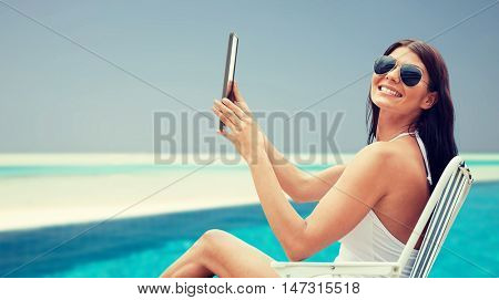 summer vacation, tourism, travel, holidays and people concept - smiling young woman with tablet pc computer sunbathing in lounge or folding chair over beach and swimming pool background