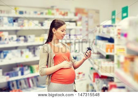 pregnancy, medicine, pharmaceutics, health care and people concept - happy pregnant woman reading label on medication jar at pharmacy