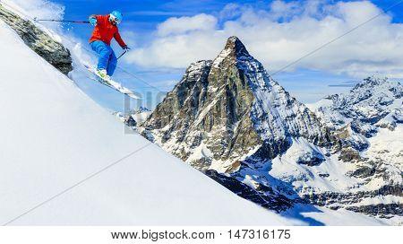 Man jumping from the rock, skiing on fresh powder snow with Matterhorn in background, Zermatt in Swiss Alps.