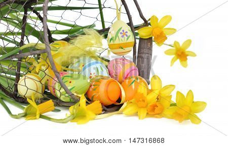 narcissus and eggs in a basket overturned on white background