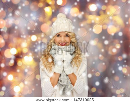 people, christmas, holidays and new year concept - happy smiling beautiful woman in winter hat, scarf and mittens over holidays lights and snow background