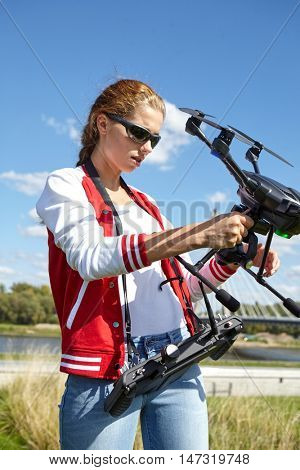 A woman is standing and holding drone