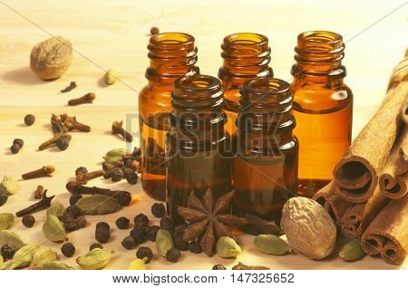 Essential oils in glass bottles maid from spices and anise, nutmeg, cardamon, cinnamon, clove, pepper on wooden background
