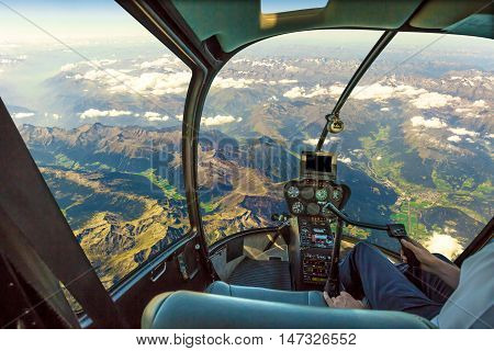 Helicopter cockpit flying on mountain landscape and cloudy sky with pilot arm driving in cabin. Spectacular aerial view of Alps mountain chain.