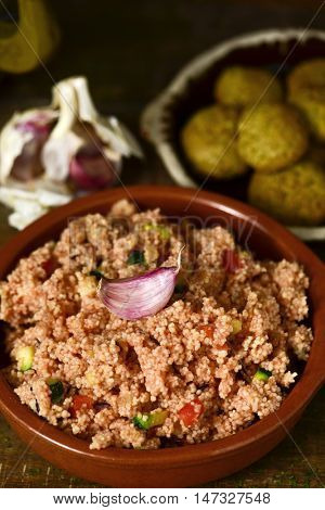 closeup of an earthenware casserole whit couscous with vegetables and some falafel in a plate in the background, on a wooden table