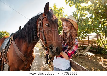 Happy lovely young woman cowgirl in hat smiling and taking care of her horse