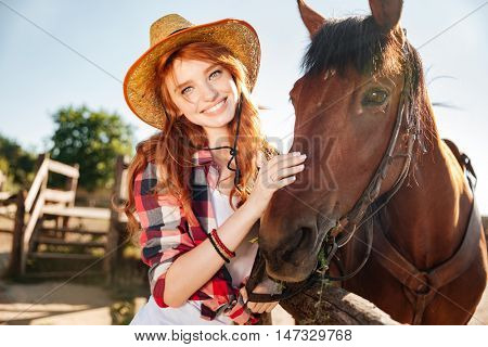 Portrait of happy redhead young woman cowgirl in hat with her horse