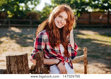Happy cute young woman cowgirl standing and smiling on farm