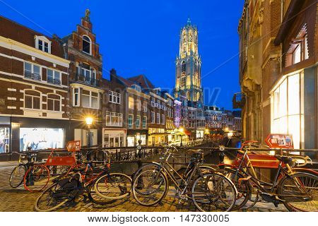 Dom Tower, bridge, bikes and canal Oudegracht in the night colorful illuminations in the blue hour, Utrecht, Netherlands