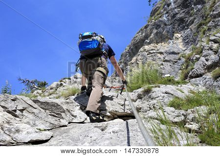 climber with equipment on a natural rock wall