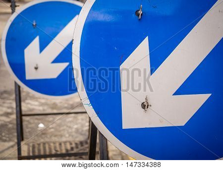 Two blue round road signs indicating on which on the lines you have to drive