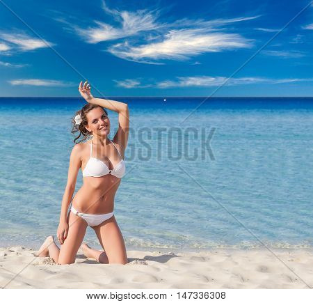 Portrait ow young brunette woman in white swim suit relaxing on tropical beach
