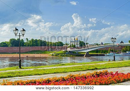 VELIKY NOVGOROD RUSSIA - JULY 15 2016. Novgorod Kremlin with footbridge and embankment along the Volkhov river in summer cloudy day - architecture landscape. Selective focus at the Kremlin