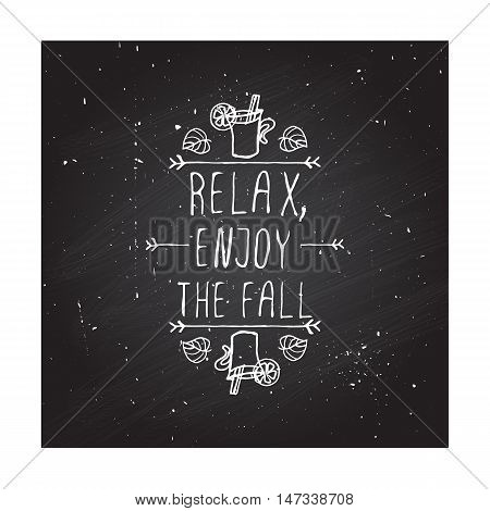 Hand-sketched typographic element with mulled wine, leaves and text on blackboard background. Relax enjoy the fall