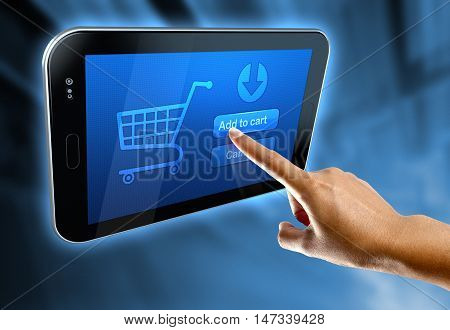 A woman's finger select a button add to cart on a digital tablet