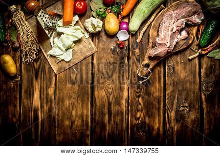 Ingredients for making soup with beef. On wooden background.