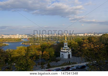 Andrew the First-called church surrounded with autumn trees. Modern Kiev buildings in background.