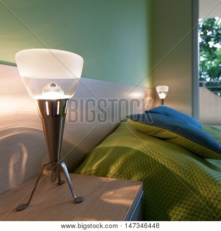 Bright green bedroom with modern bedside lamps