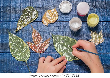 Girl paints patterns autumn leaf. Gouache brush and various autumn leaves on a blue wooden table. Children's art project. Colorful Hand-painted on dry autumn leaves