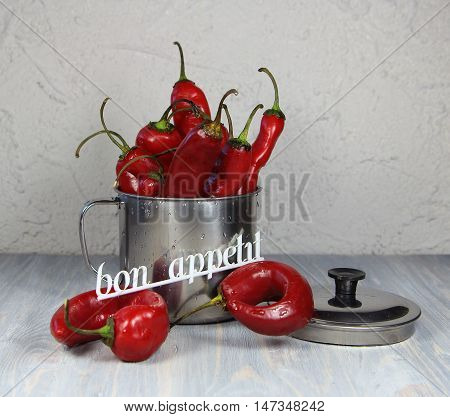 pepper red sharp in a metal mug and an inscription bon appetit
