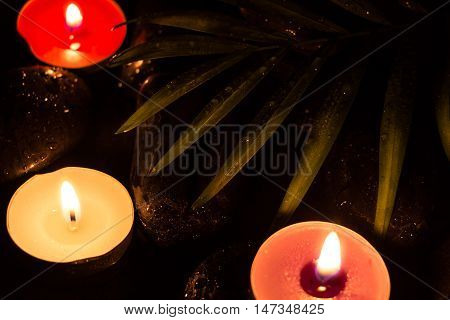 Scent Colorful Lighted Candles On Black Wet Stones And Green Leaf With Droplets, Dark Photography