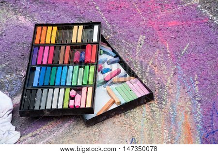 An open box of colored chalk used for drawing.