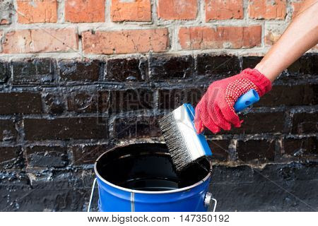 Roofer covered brick wall bitumen primer for improving adhesion during surfacing contiguity with rolled waterproofing during the installation of flat roof.
