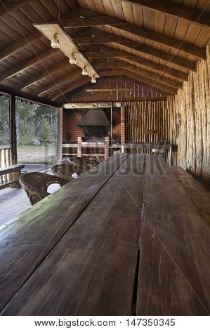 Covered veranda of a country house with long wooden table