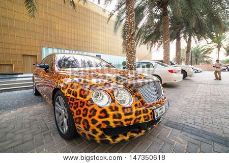 DUBAI, UAE - MARCH 30, 2014: Panther paint Bentley parked outside the Hilton Dubai Hotel on, UAE. Dubai is one of the richest cities in the world with many luxury cars on streets.