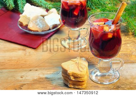 Mulled Wine With Cinnamon Sticks And Christmas Bell-formed Cookies