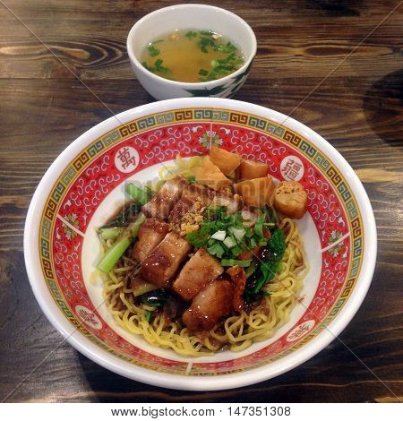 Thai Dried Yellow Egg Noodle with Meatball and soup Roasted Red Pork Crispy Pork Spring Onion Dumpling with Pork inside all in a bowl for lunch or dinner
