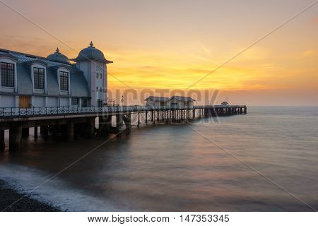 Penarth Pier with pebble beach and the Bristol Channel Wales United Kingdom at sunrise.