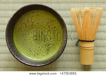 Japanese Matcha green tea in a chawan or traditional ceramic bowl with a chasen or bamboo whisk