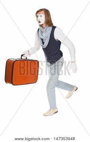 mime actor with a frightened face is running with a suitcase in his hand