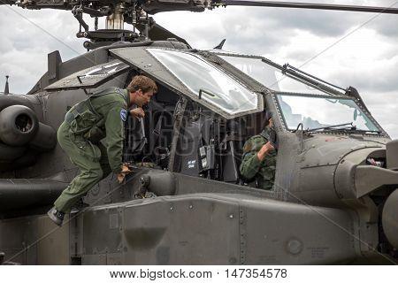 GILZE-RIJEN NETHERLANDS - JUN 20 2014: Pilot getting into an AH-64 Apache attack helicopter.