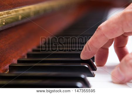 Close up of a male hand on piano with index finger on a black key selective focus on the tip of index finger blur background