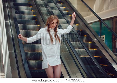 Girl coming down the escalator at the mall