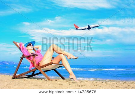 Young sexy woman Relaxing on the beach with an airplane passing behind her - Travel concept