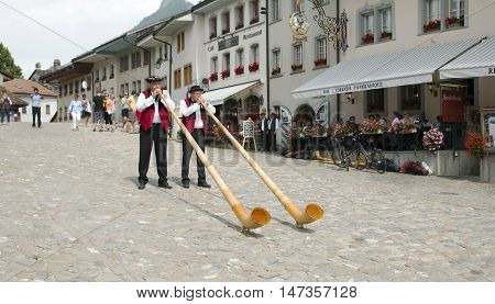 Gruyere, Switzerland - July 19, 2014 - Traditional Swiss musicians play the folk national musical instrument alphorn in a historical costumes in Gruyere village.